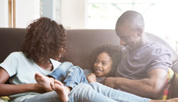 African-American-Family-on-couch-laughing-Web