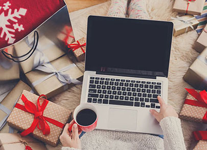 Depicted is a woman with a laptop holding coffee, surrounded by presents that are wrapped with a holiday theme